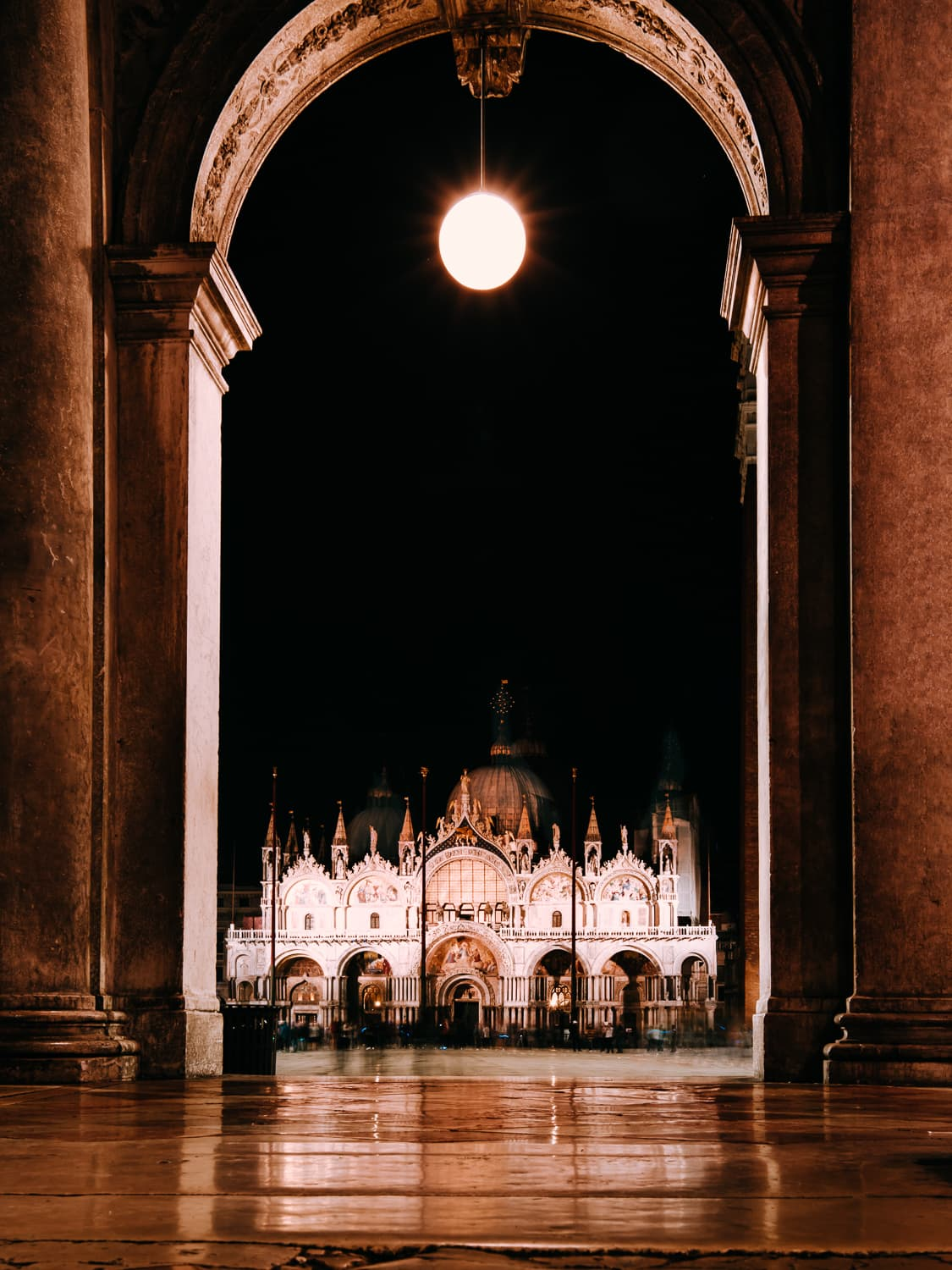 A look at the Basilica San Marco at night, photographed between some columns and arches.