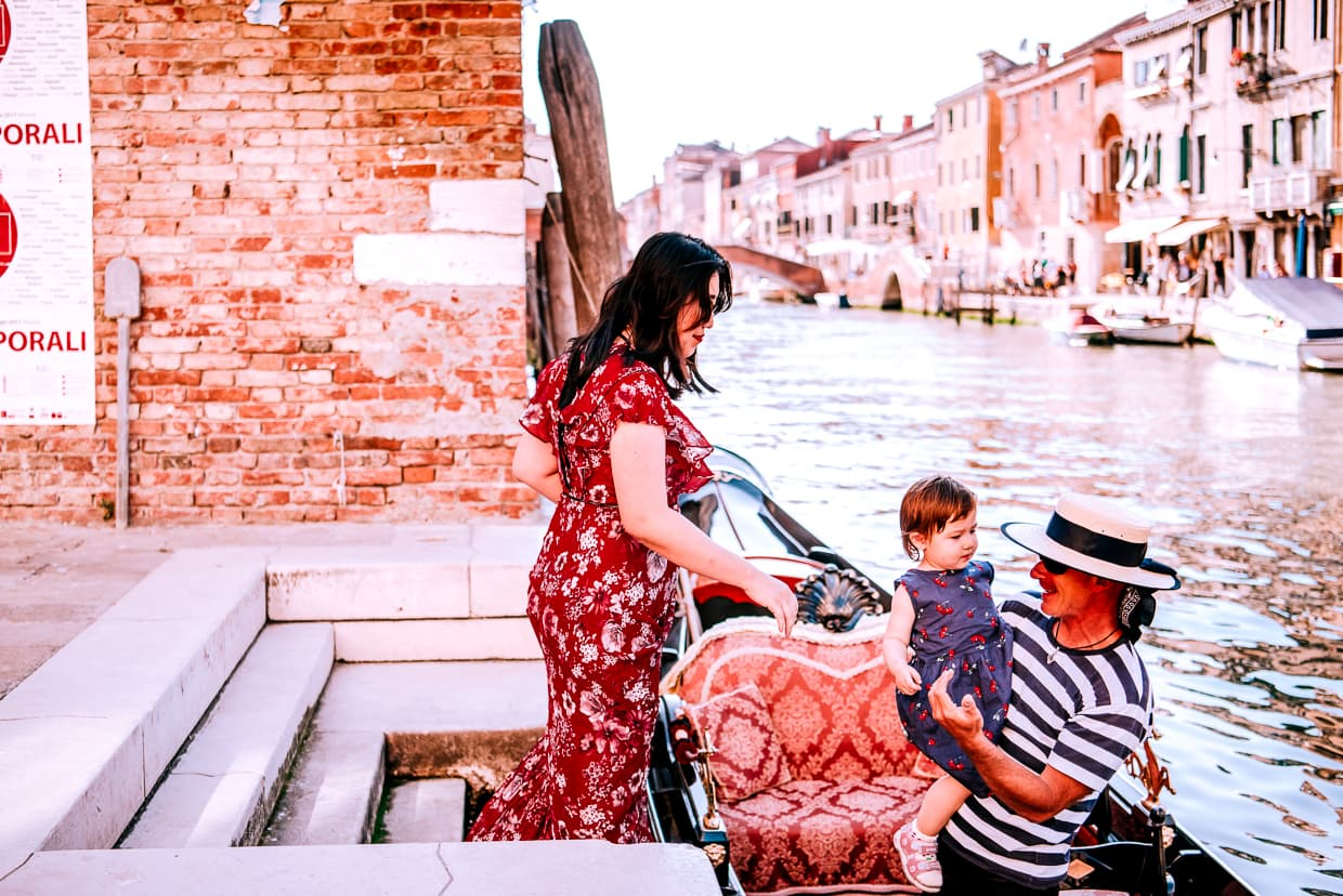 A gondolier helps Lisa into his gondola as we get ready for a photo shoot in Venice, Italy.