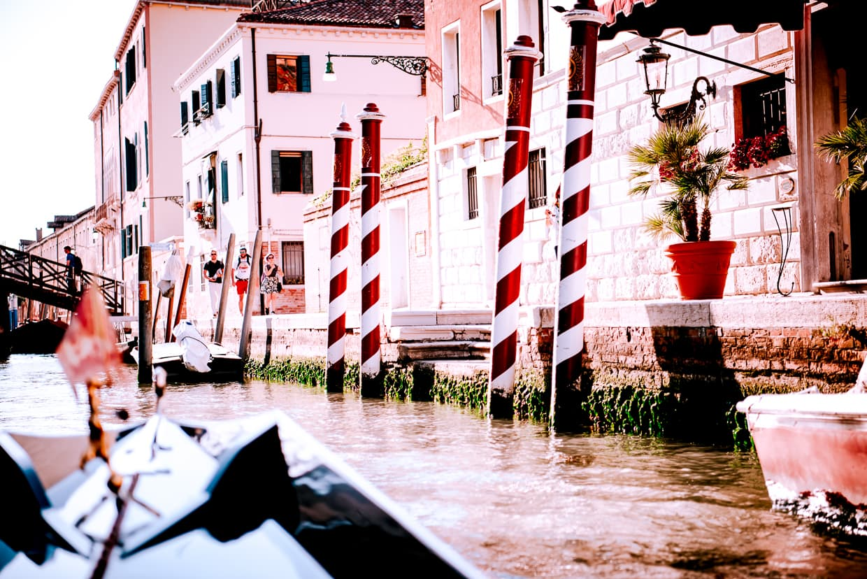 Striped mooring poles in Venice, Italy that look like candy canes or barber poles.