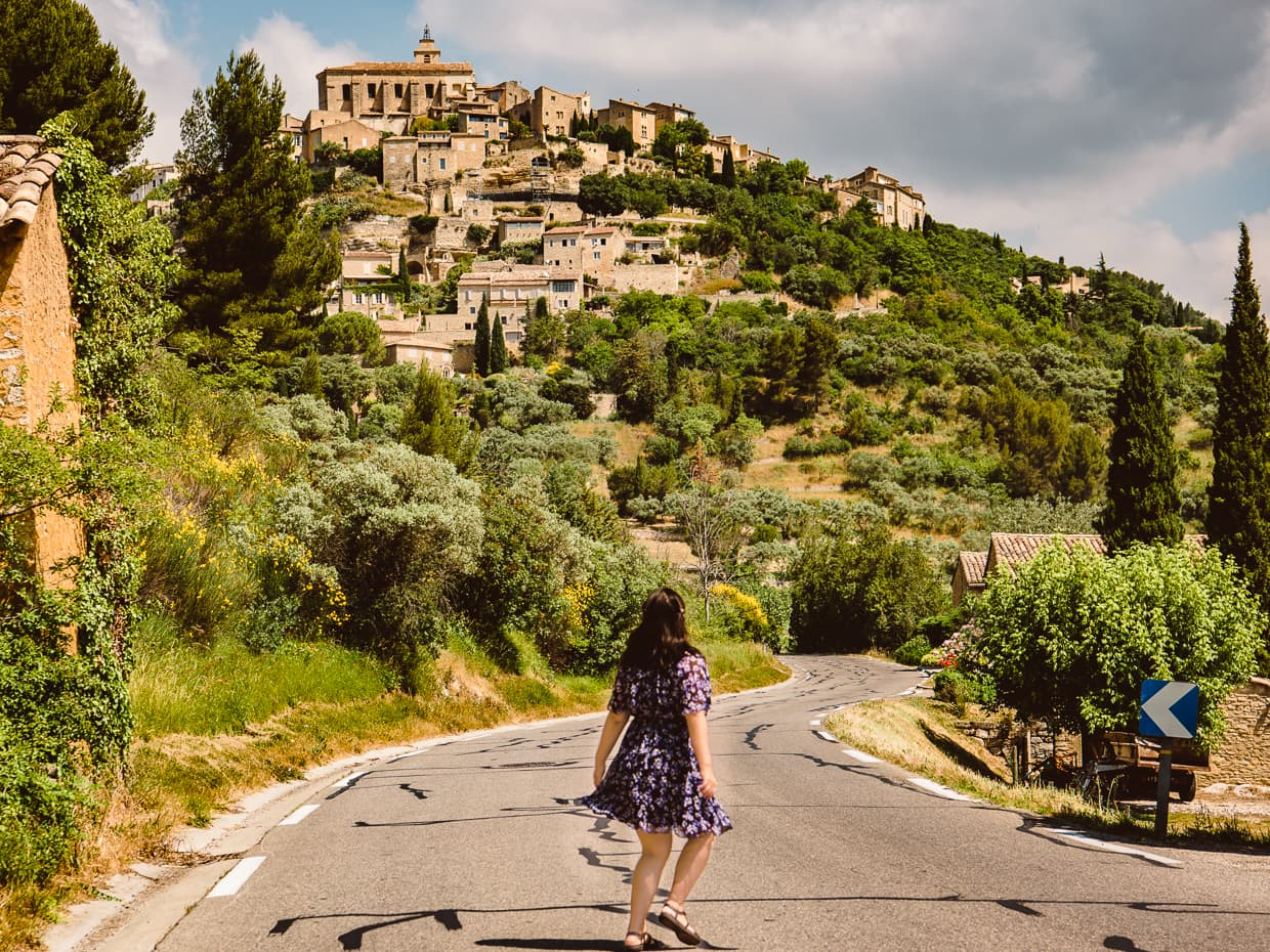 Walking down the road in Provence, with the cliffside town of Gordes, France in the background.