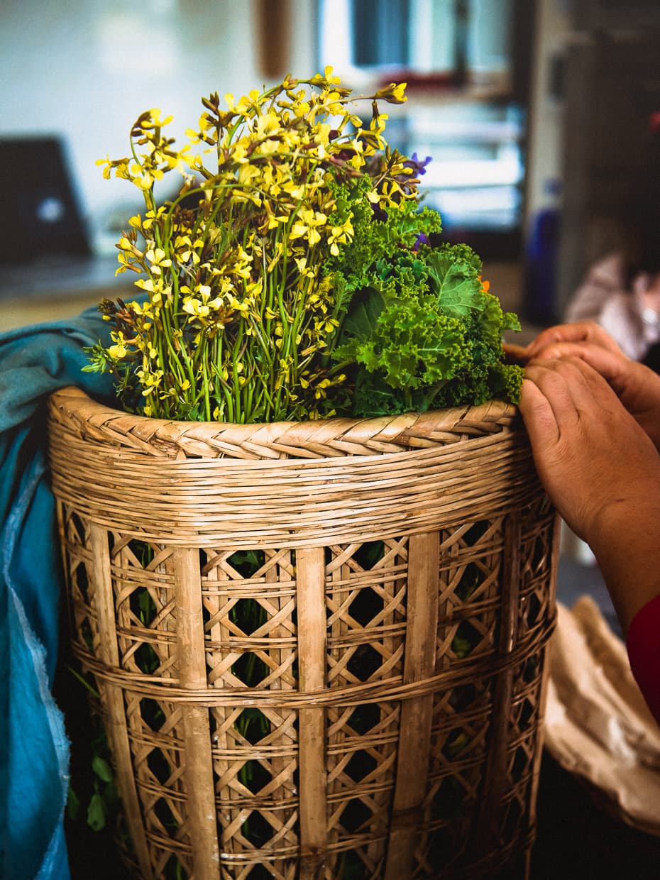 A basket of flowers and fresh vegetables in our Dali, China cooking class.
