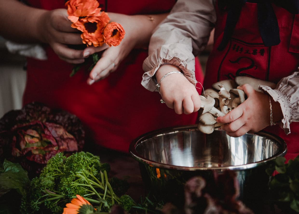 Toddler hands preparing mushrooms during cooking lesson.