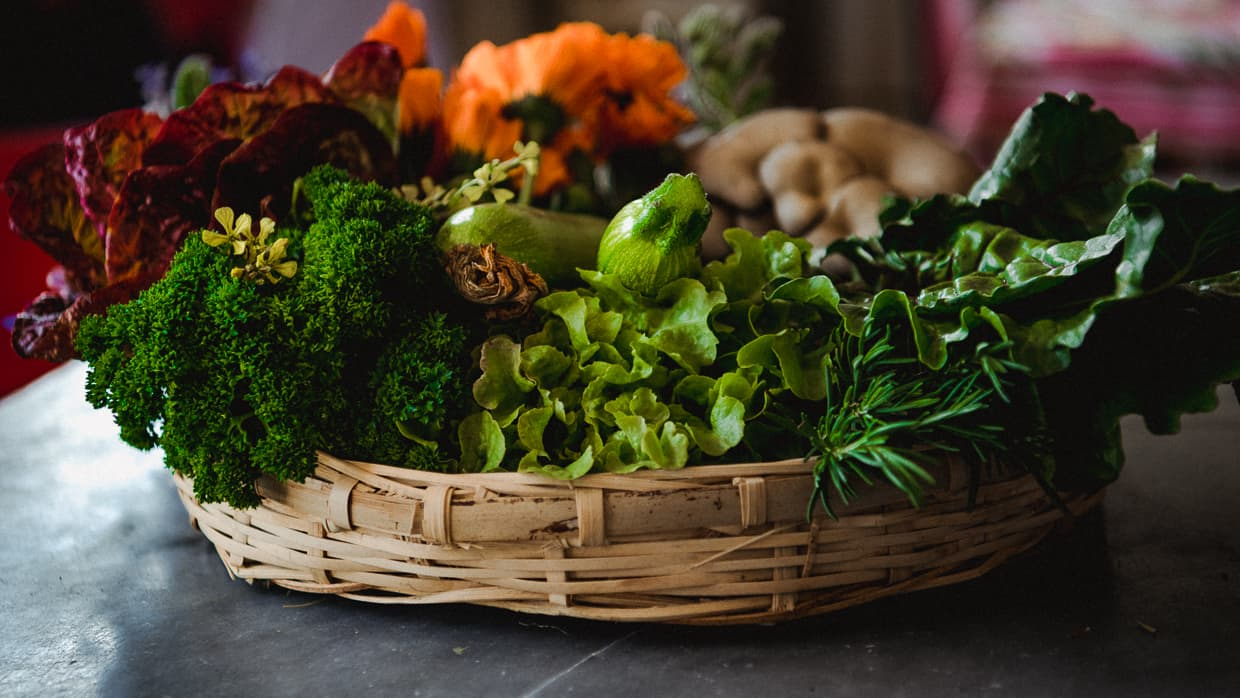 A basket of fresh vegetables and flowers from the farmers market in Dali.