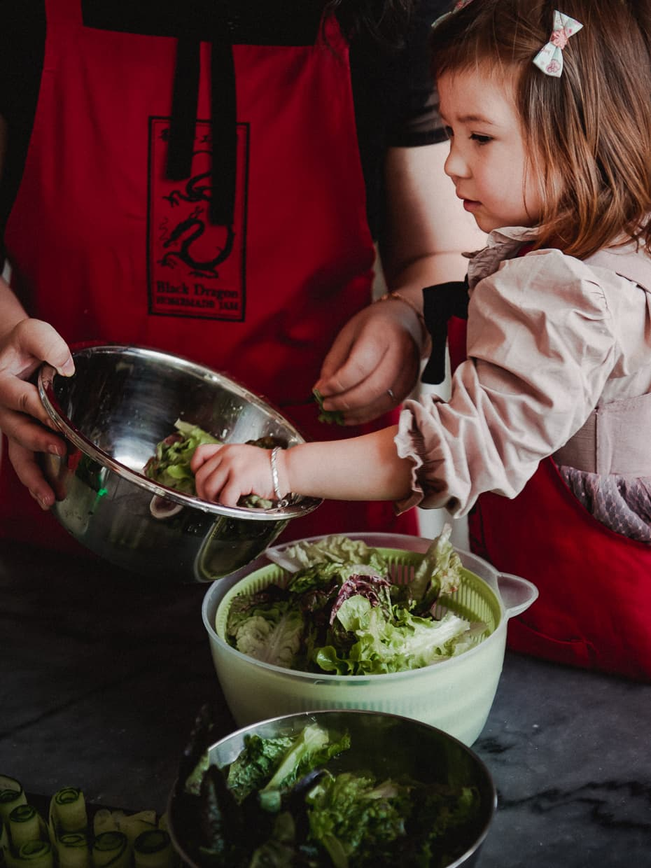 Toddler helping to prepare a salad.