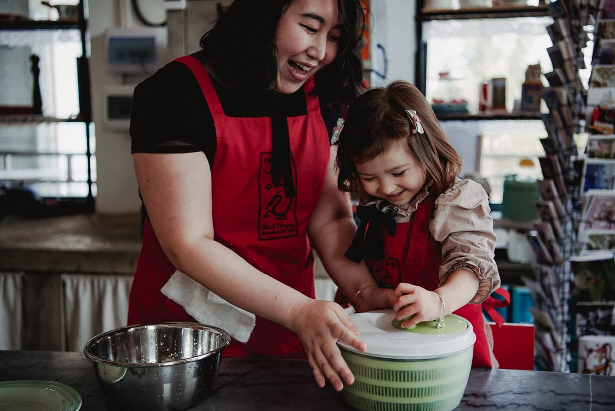 Mother and daughter using salad spinner during cooking class.