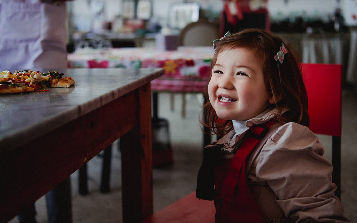 A happy toddler in Dali, China's Black Dragon Cafe.