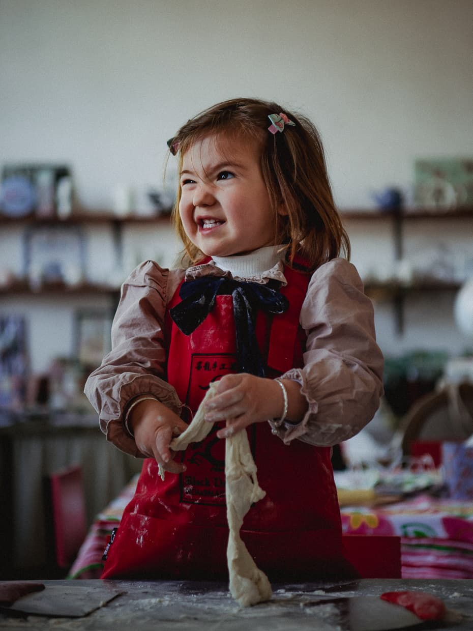 Toddler making faces as she plays with dough.