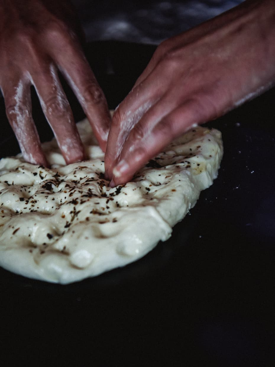 Putting oil and seasoning on focaccia bread.