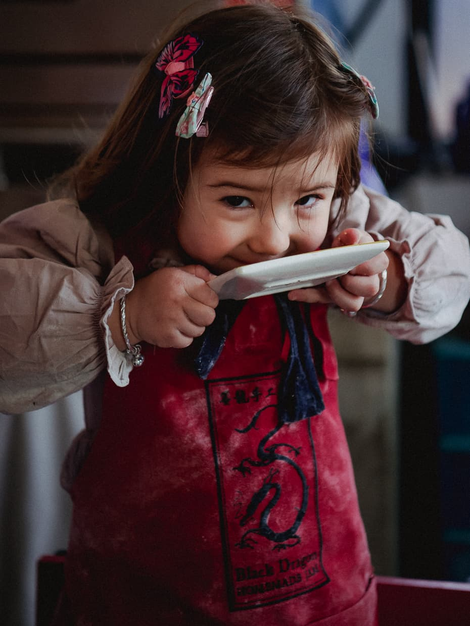 Toddler licking plate during cooking class.