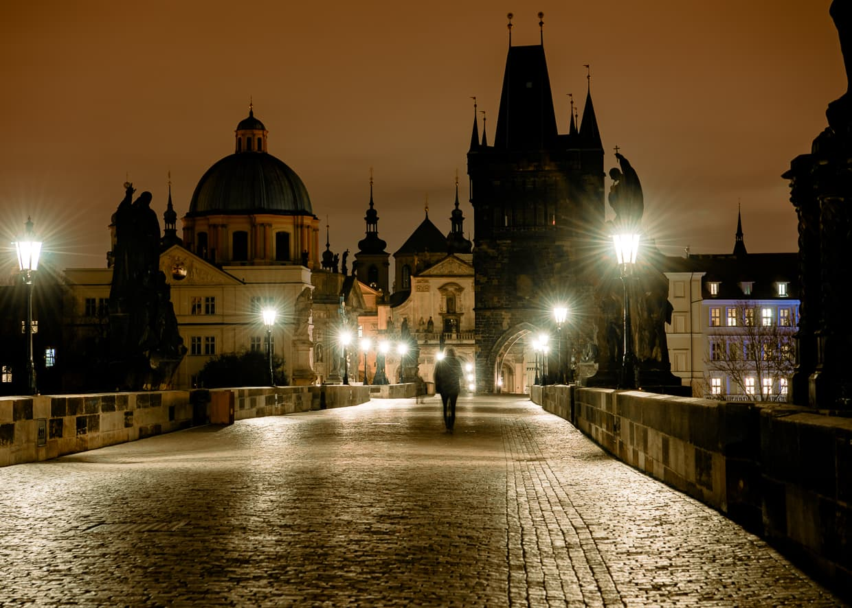 A single person walking on the Charles bridge in Prague.