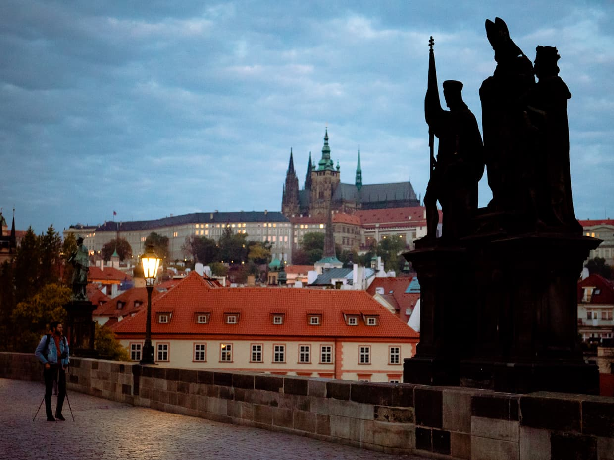A statue on the Charles bridge with Prague castle in the background.