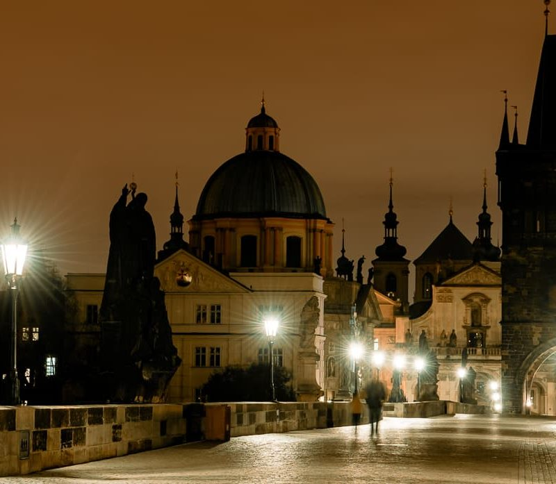 Prague's Charles Bridge at night with lamp light.