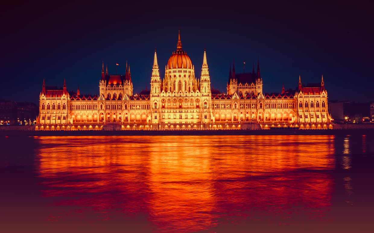 The Hungarian Parliament Building at night with the lights on.