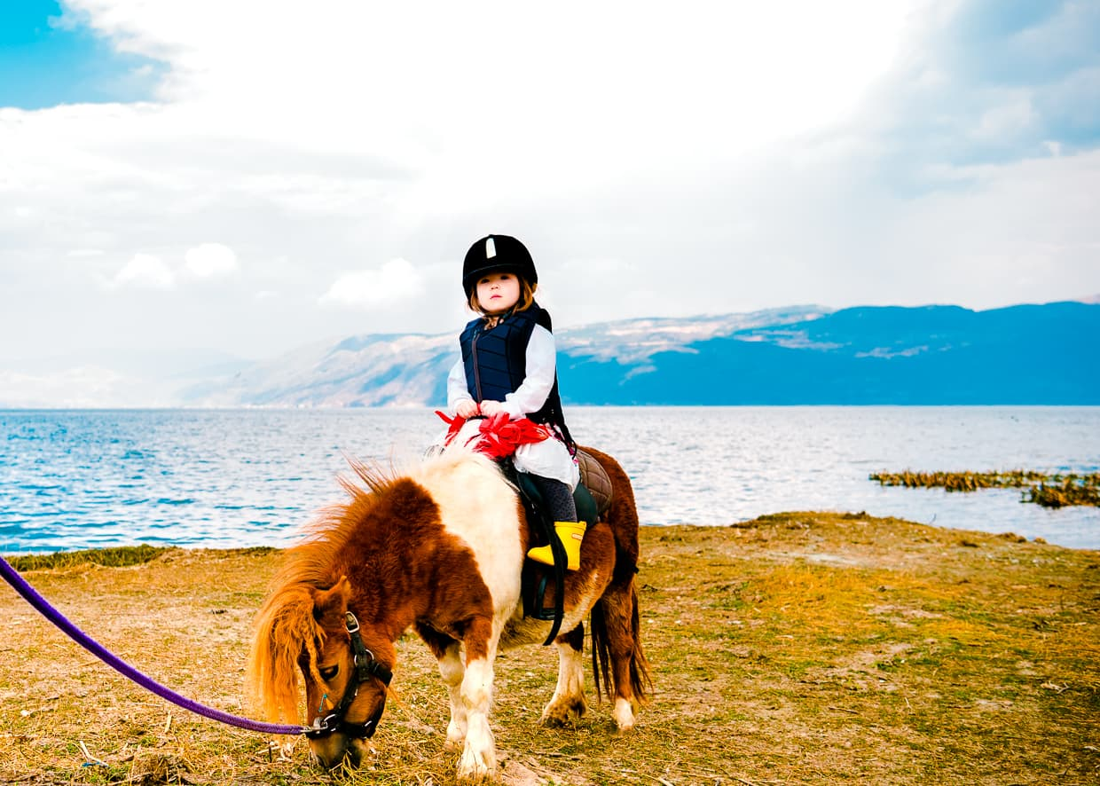 Lisa on a pony by Erhai Lake in Dali, China.