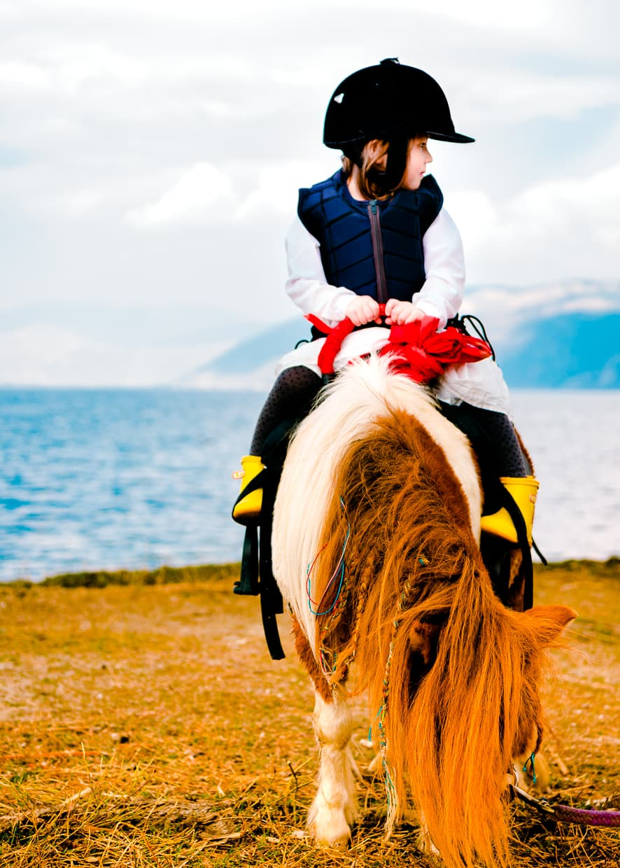 Sitting on a pony by Erhai Lake.