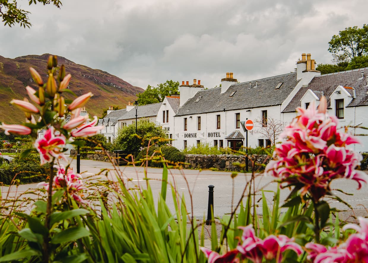 A lovely street of quaint houses and flowers in Dornie, Scotland.