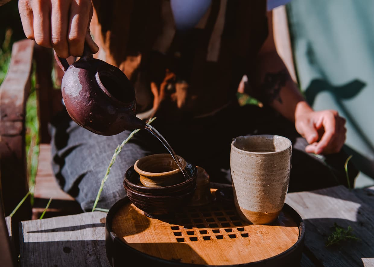 Pouring a cup of tea from a clay pot.