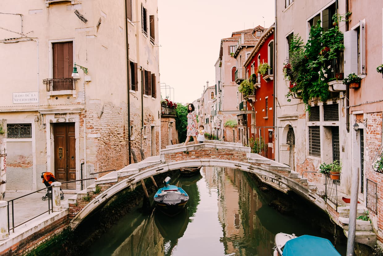 A stone bridge over a Venice canal.