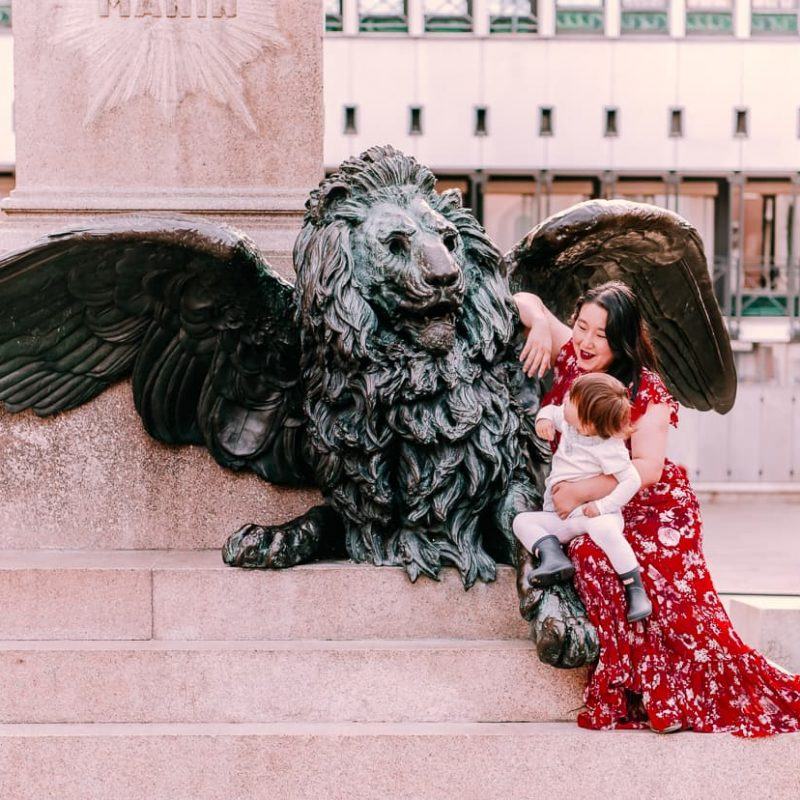 Child in Venice, Italy next to winged lion statue.