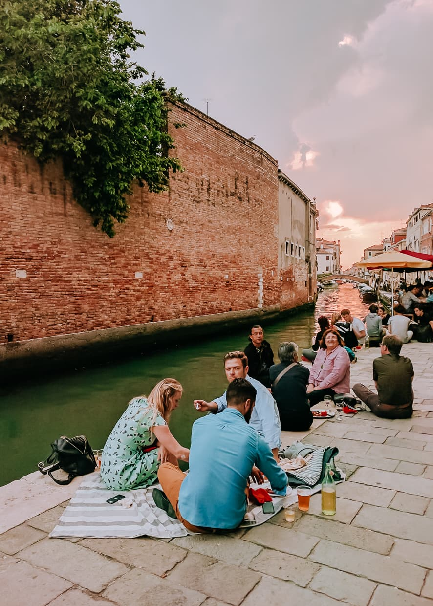 People sitting in the streets of Venice.