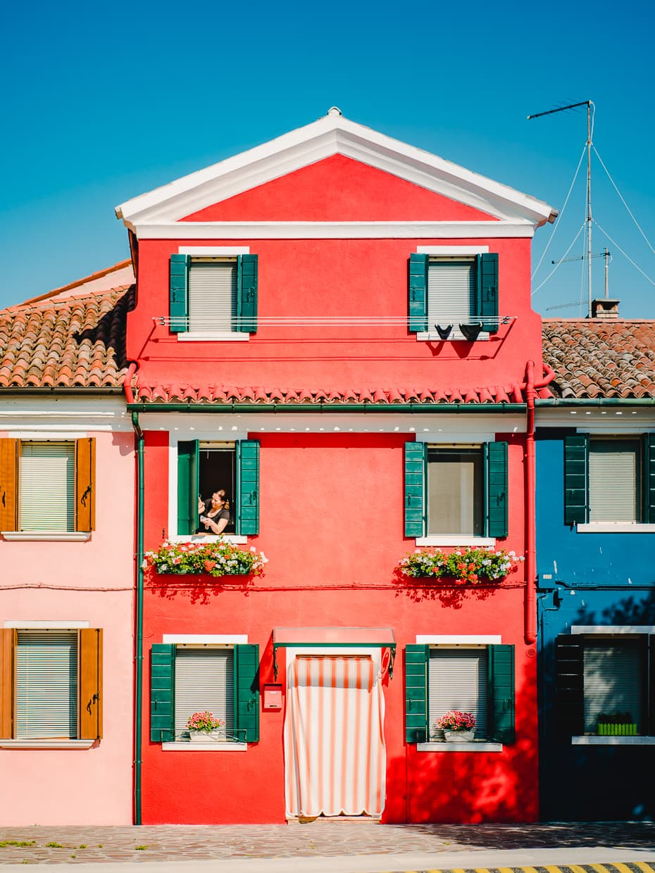 A Burano house with a woman in the window.