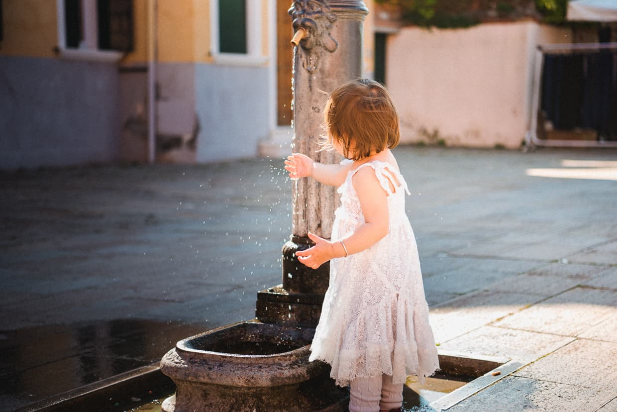 Girl playing with fountain. Burano, Italy.
