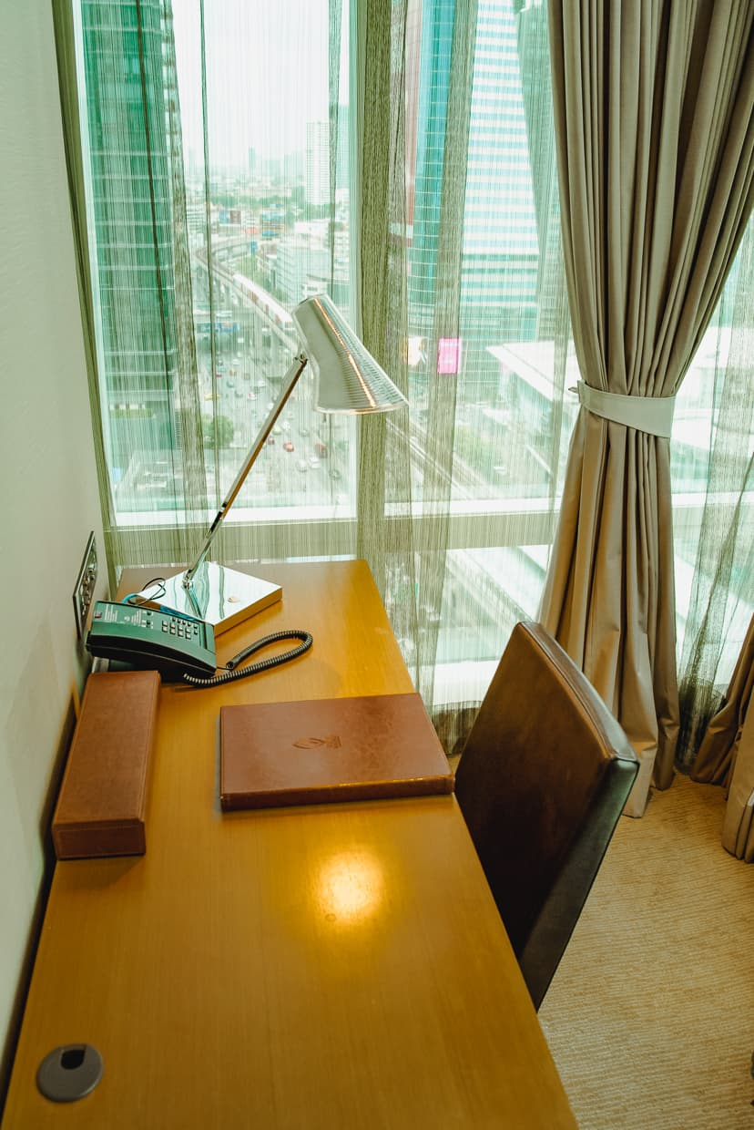 A hotel desk with Bangkok, Thailand out the window.