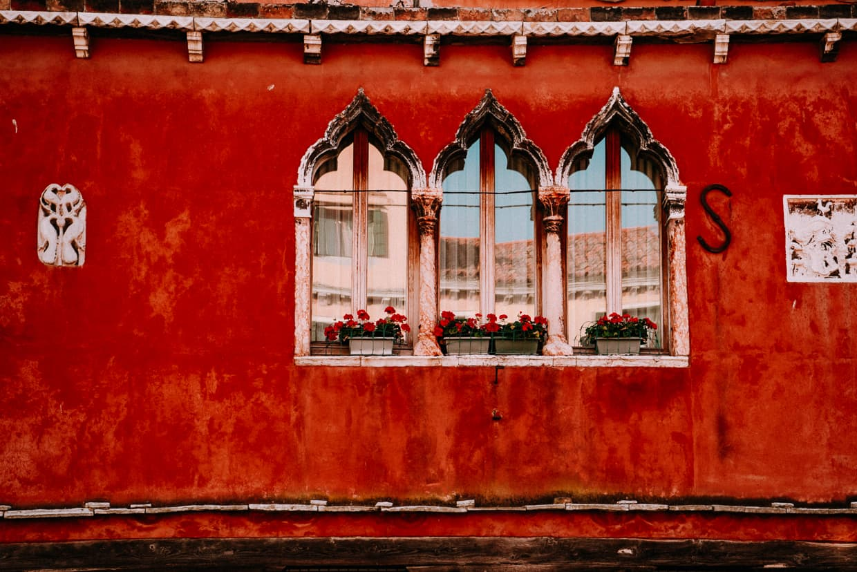 Arched windows on a red wall in Murano, Italy.