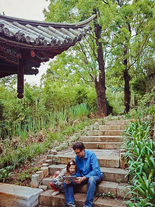Father and daughter reading kindle books on steps in China.