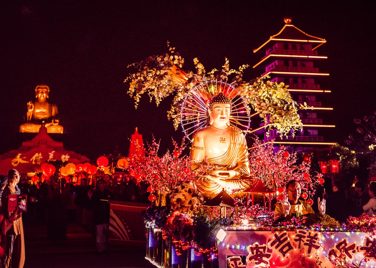A buddha parade float in front of the Big Buddha Statue of Fo Guang Shan.