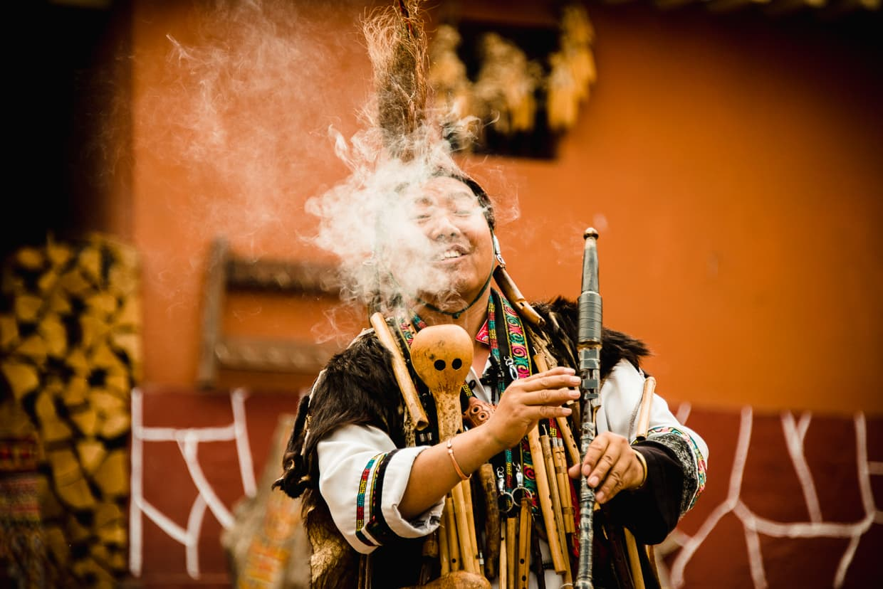 A performer smoking a traditional pipe in the Yunnan Ethnic Village.