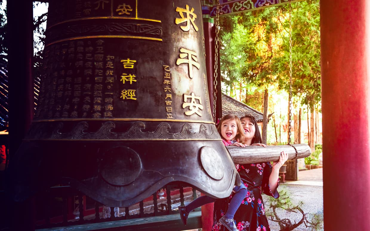 Striking the giant bell on top of Lion Hill in Lijiang.