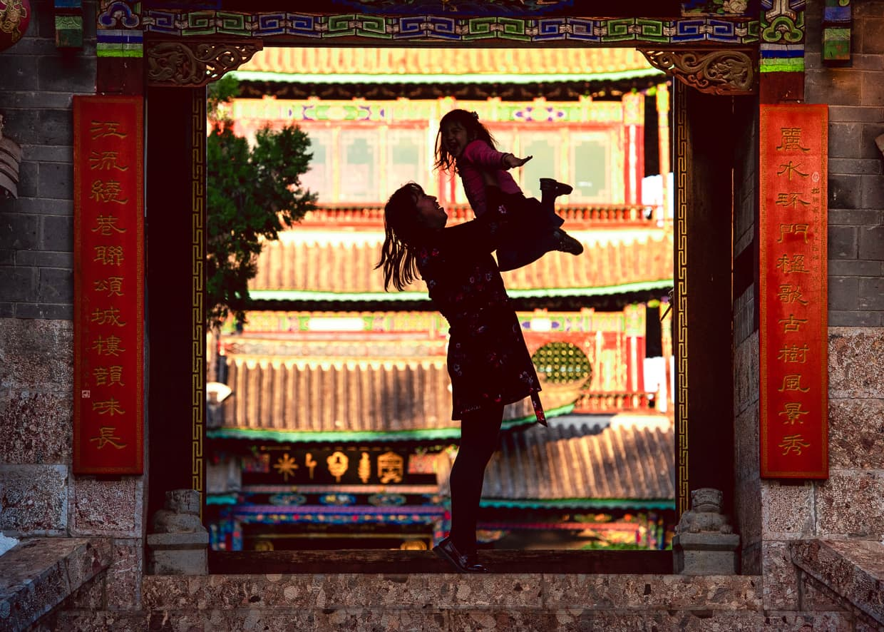 Playing in the gate in front of Wangu Tower in Lijiang.