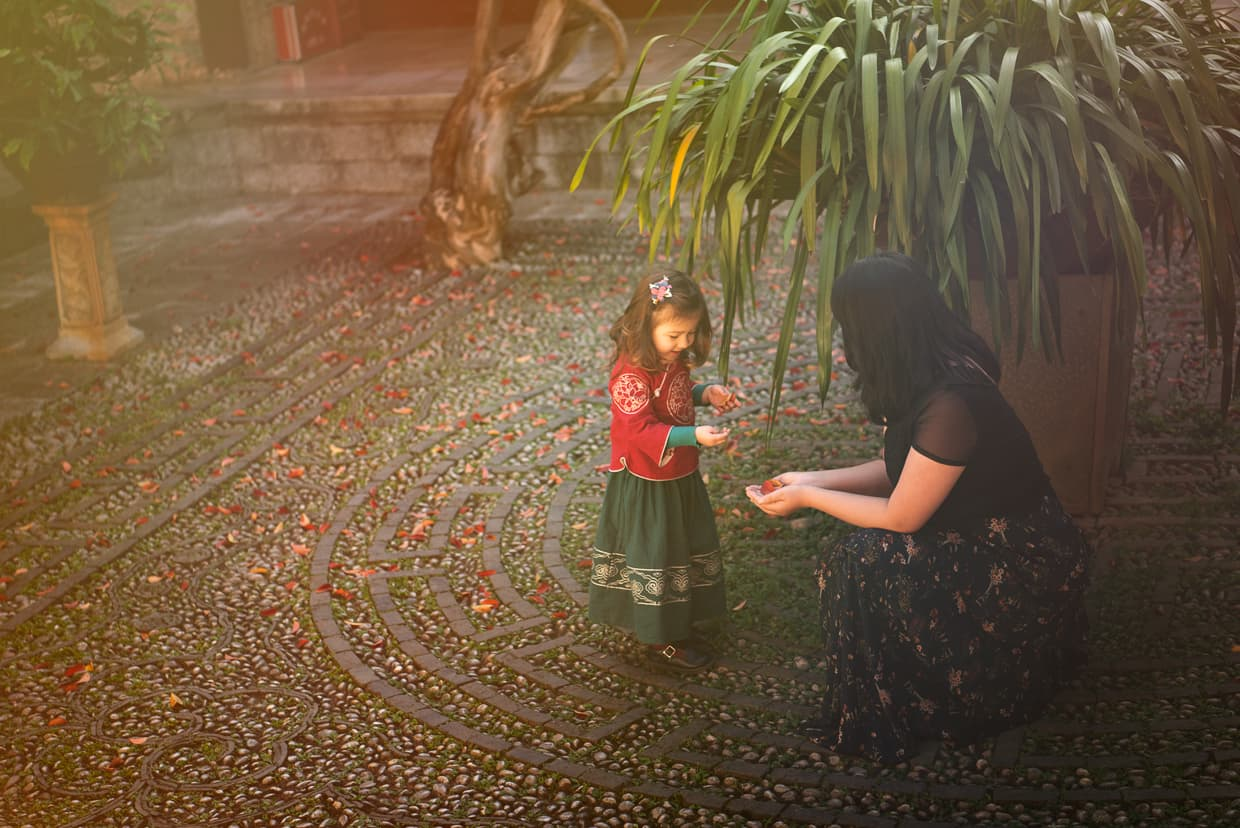 Mother and daughter gathering leaves in a Chinese palace courtyard.