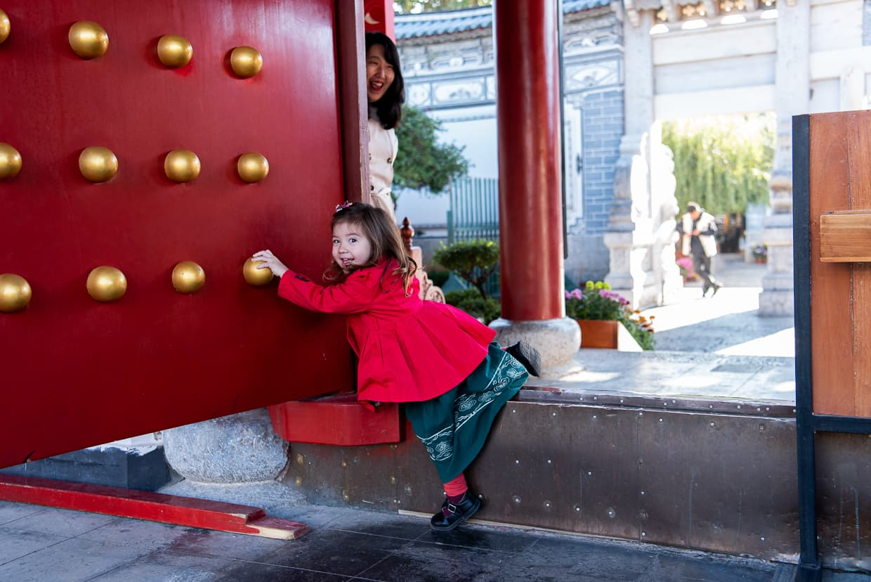 Climbing over a high Chinese doorstep in Mufu Palace. Lijiang, China.