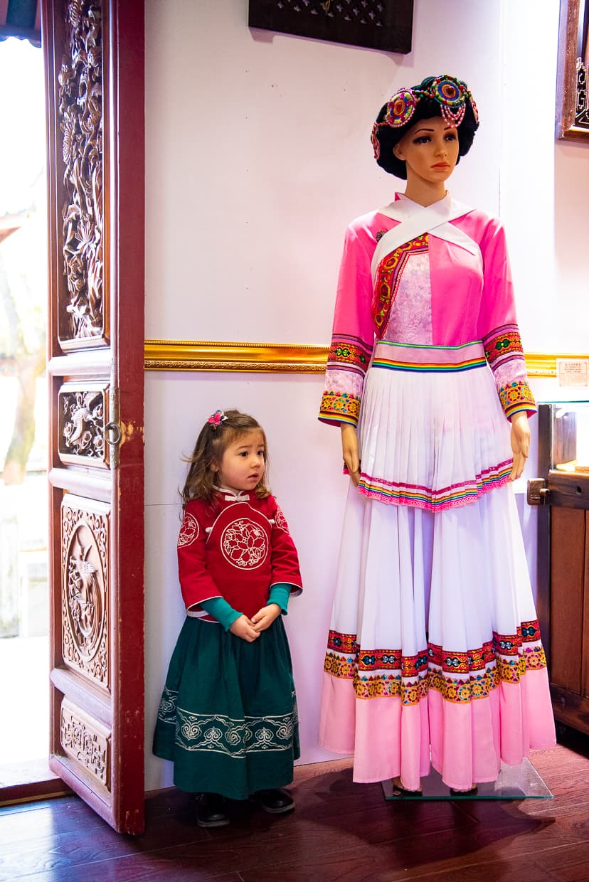 Posing next to a mannequin wearing traditional Naxi minority clothing.