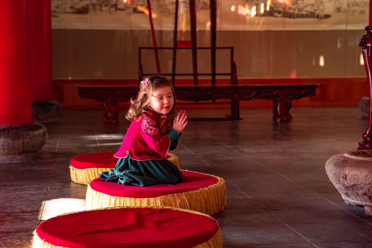 Girl praying in a Buddhist temple in Lijiang, China.