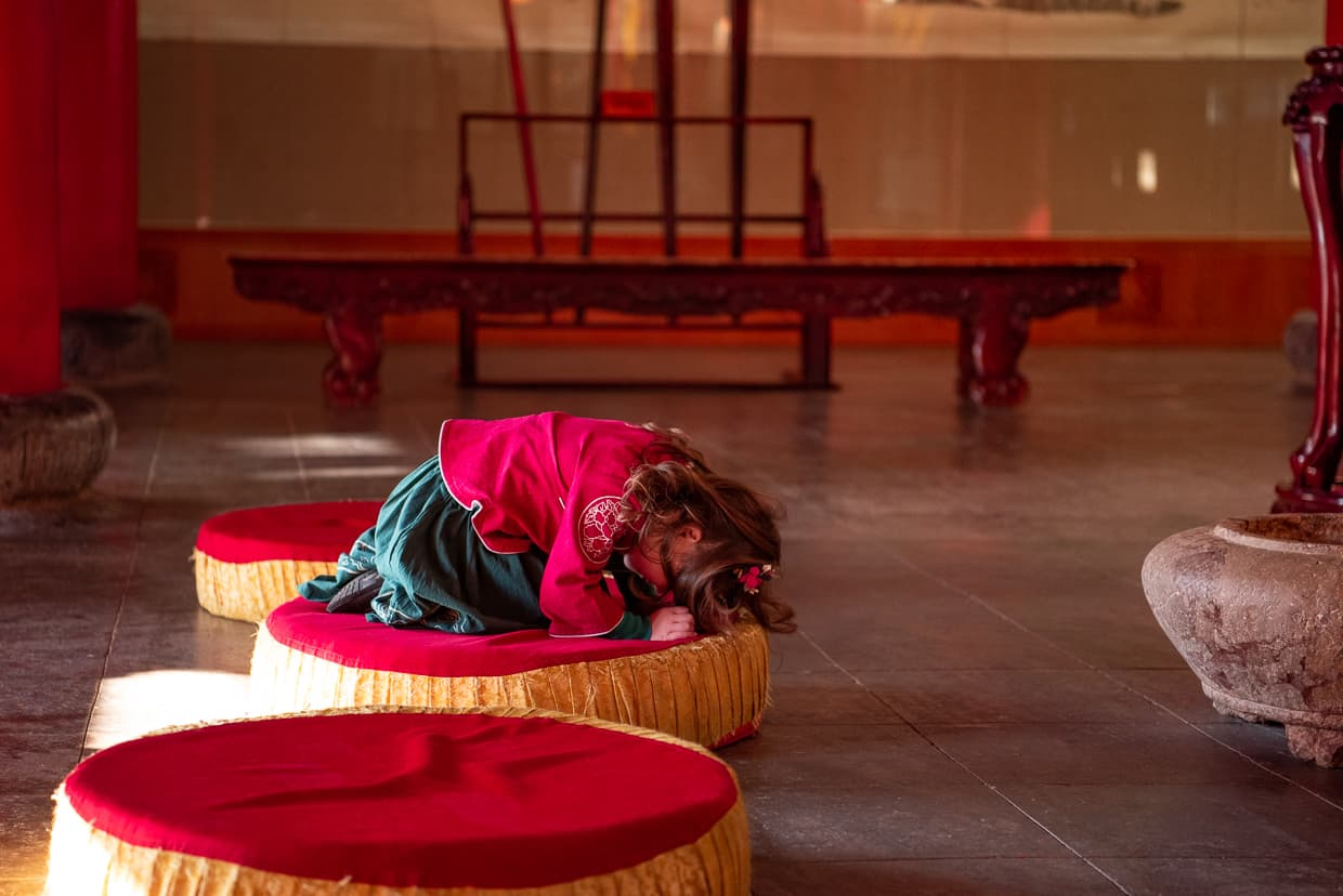 Little girl bowing in traditional Chinese clothing in a Buddhist Temple.