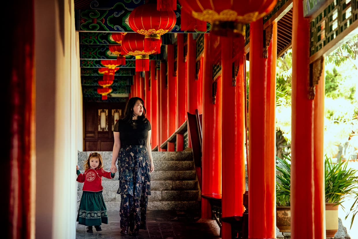 Walking by red columns and Chinese lanterns in Mufu Palace. Lijiang, China.