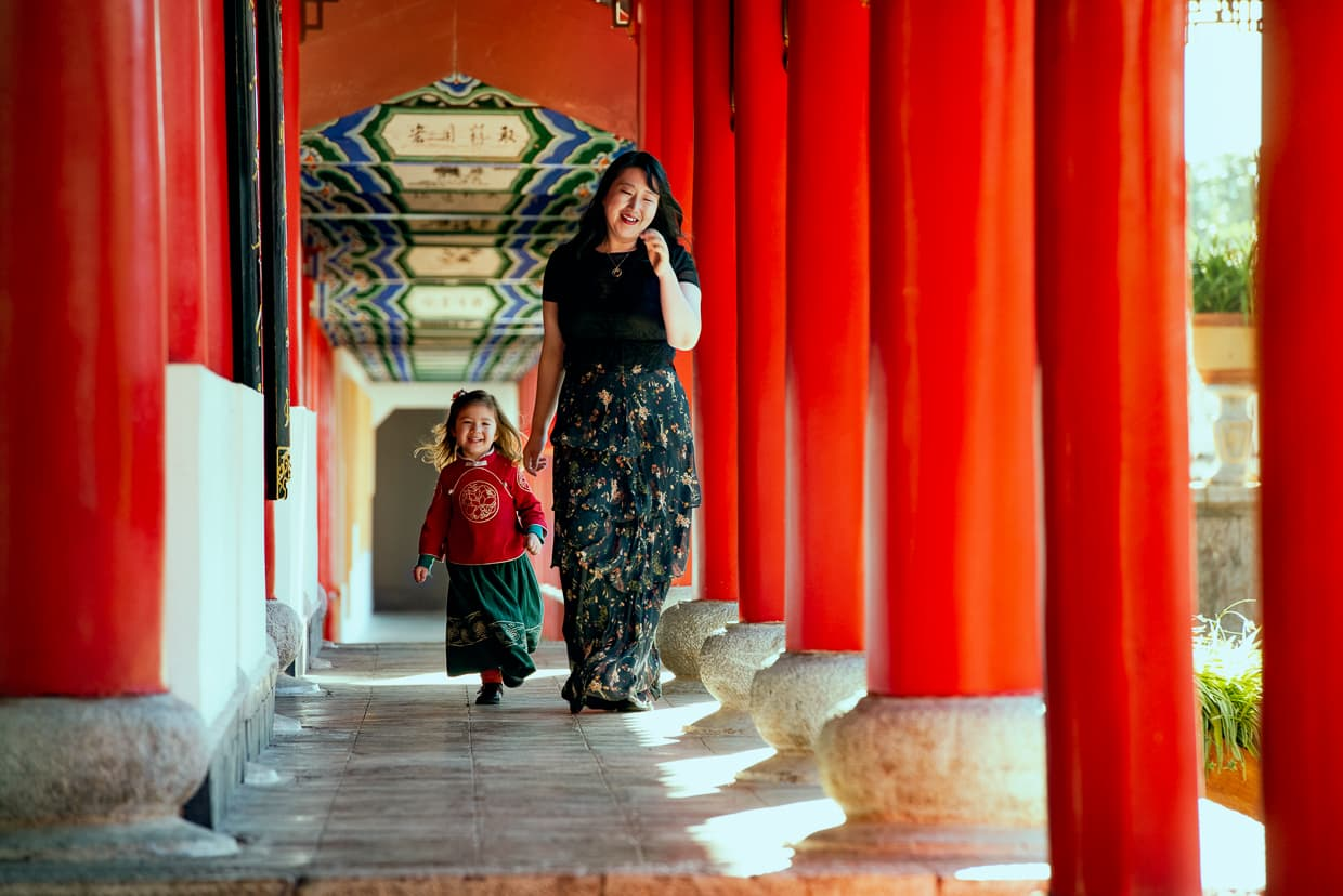Walking down a corridor of red columns in a Chinese Palace.