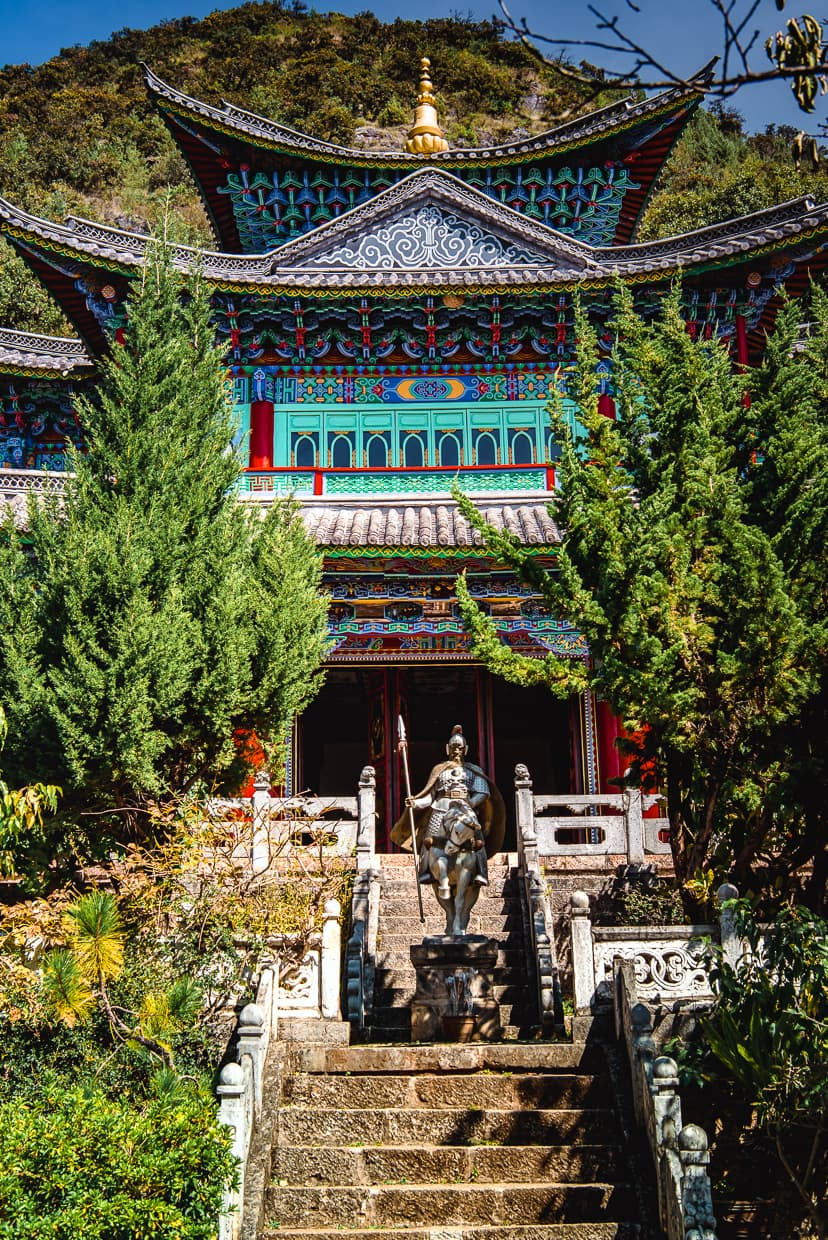 A buddhist temple in Lijiang, China with a statue and stairs.