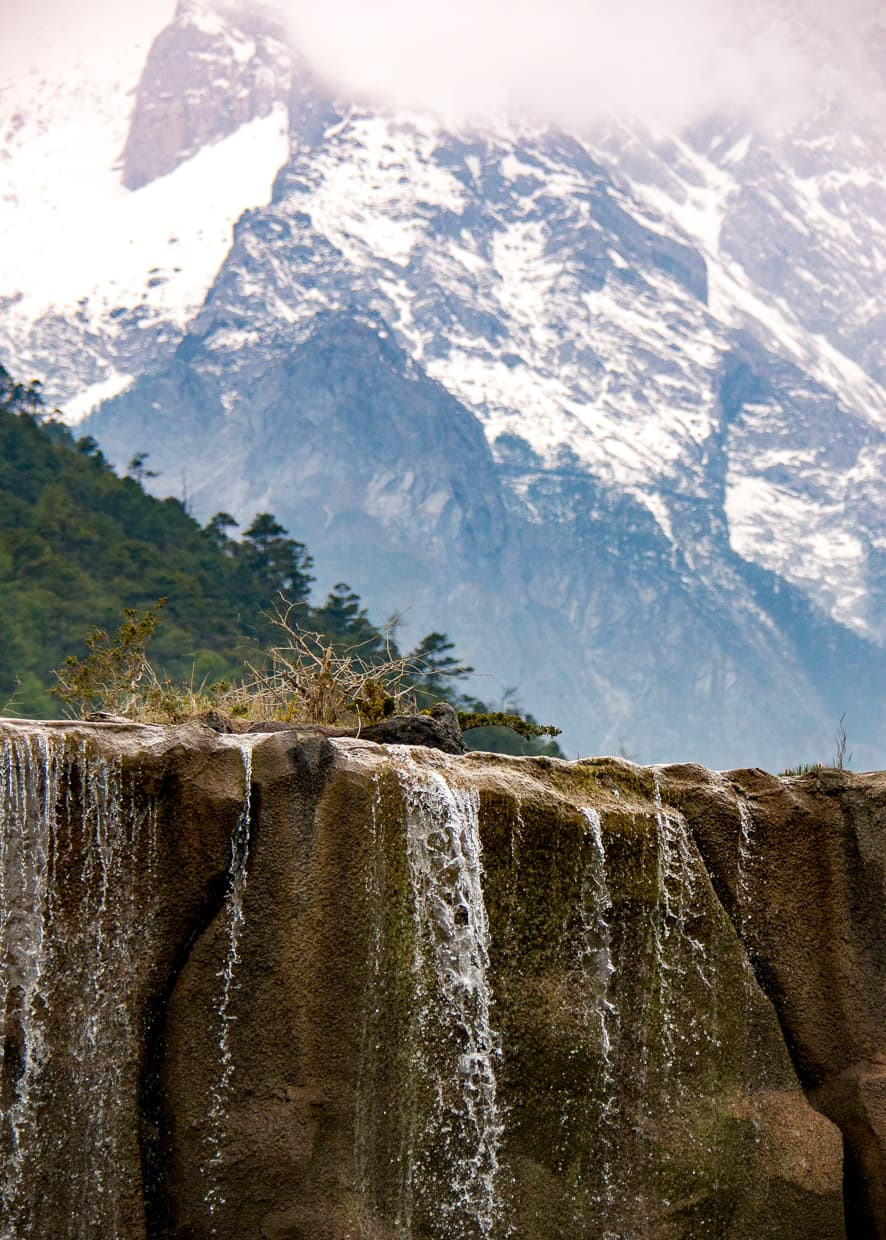 A waterfall in front of the Jade Dragon Snow Mountain in Lijiang, China.