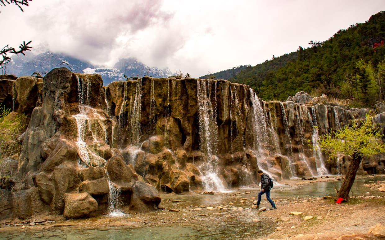 Walking in front of a Lijiang Waterfall near the Jade Dragon Snow Mountain.