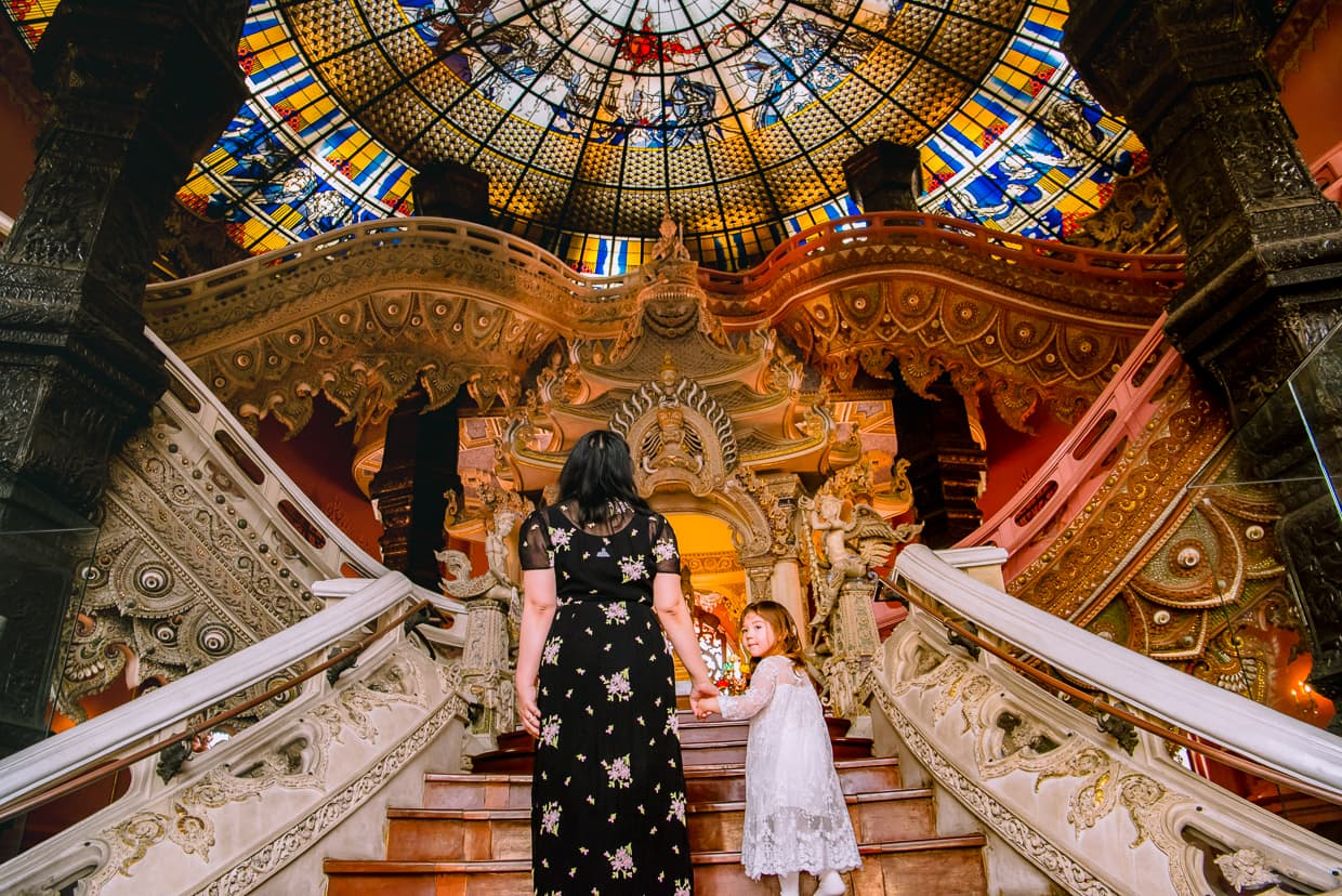 Mother and Daughter entering the Erawan Museum and walking up the stairs.