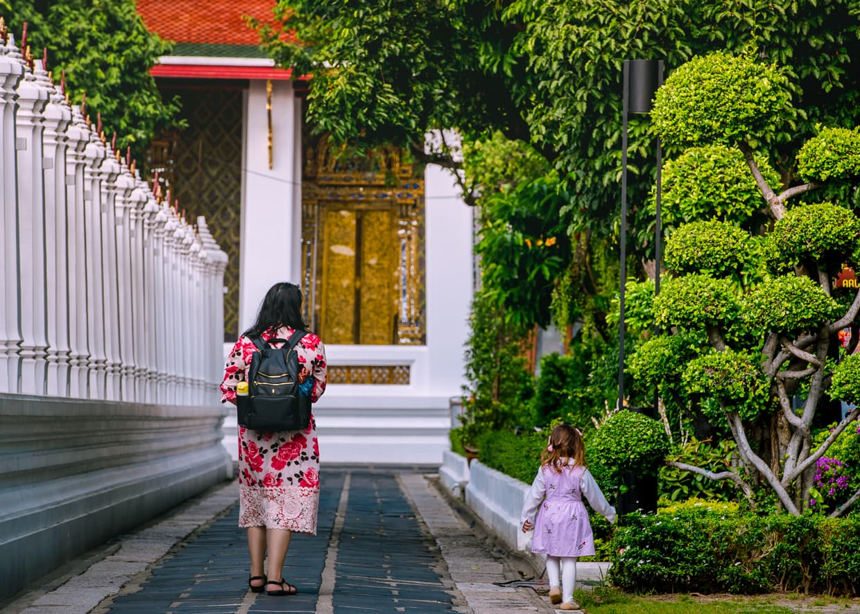 Family walking in the gardens outside Wat Arun.