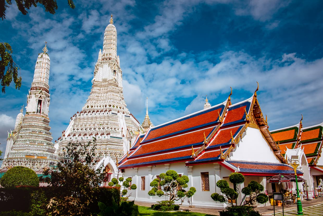 Wat Arun in Bangkok, Thailand under a blue sky.