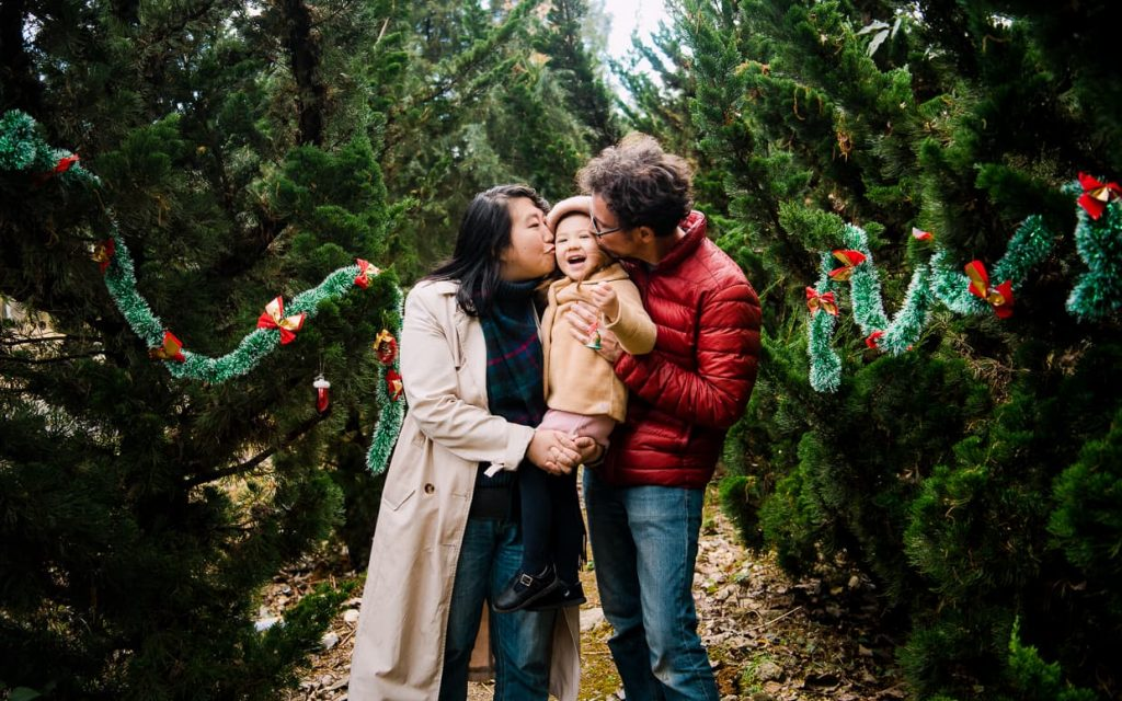 A family Christmas photo in Dali, China. Mommy and Daddy kiss Lisa on the cheeks.