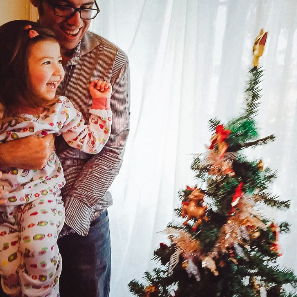 Father and daughter decorating the Christmas tree.