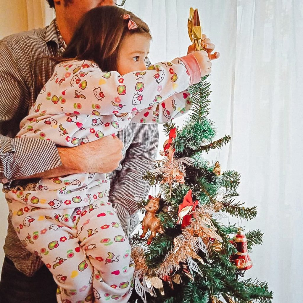 Father holding daughter to put a star on the Christmas Tree.