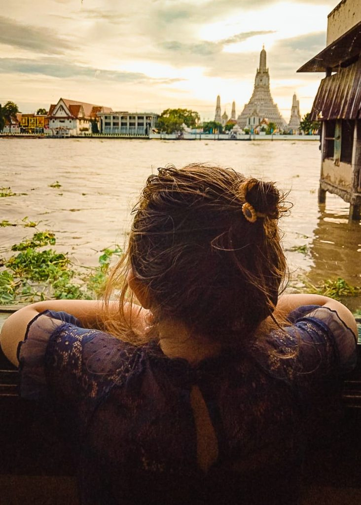 Little girl looking out the restaurant window at wat arun.